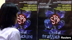 FILE - A Filipino girl looks at posters condemning child trafficking inside a shelter for runaway child laborers in Manila.