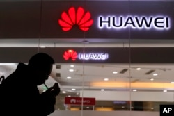 FILE - A man lights a cigarette outside a Huawei retail shop in Beijing, Dec. 6, 2018.