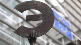 A statue shows the Euro symbol flipped, at the European Commission headquarters in Brussels, Belgium, March 7, 2012.