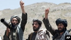 FILE - Taliban fighters react to a speech by their senior leader in the Shindand district of Herat province, Afghanistan, May 27, 2016.