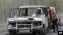 ຊາວບ້ານທ້ອງຖິ່ນຄົນນຶ່ງ ຊ່ອງເບິ່ງລົດ ທີ່ຖືກທຳລາຍ ໃນການໂຈມຕີ ດ່ານກວດແຫ່ງນຶ່ງ ທີ່ຄວບຄຸມໂດຍ ຝ່າຍນິຍົມຣັດເຊຍ ໃນໝູ່ບ້ານ Bulbasika ໃກ້ໆເມືອງ Slovyansk ພາກຕາເວັນອອກຂອງຢູເຄຣນ, ວັນອາທິດ ທີ 20 ເມສາ 2014.
