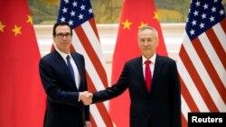 美国财政部长姆努钦(左)和中国副总理刘鹤在北京钓鱼台国宾馆举行美中高级别贸易谈判前握手。(2019年2月14日)