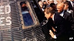 Astronaut John Glenn, right, shows his Friendship 7 space capsule to President John F. Kennedy at Cape Canaveral, Florida, in 1962