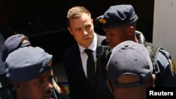 FILE - South African Olympic and Paralympic sprinter Oscar Pistorius is escorted to a police van after his sentencing at the North Gauteng High Court in Pretoria, Oct. 21, 2014.