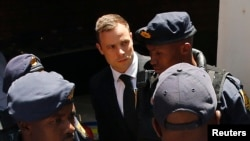 FILE - South African Olympic and Paralympic sprinter Oscar Pistorius (C) is escorted to a police van after his sentencing at the North Gauteng High Court in Pretoria, Oct. 21, 2014.