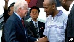 지난 2010년 8월 25일부터 사흘간 북한 평양을 방문한 지미 카터 전 미국 대통령이 27일 순안공항에서 북한에 억류됐다 풀려난 미국인 아이잘론 말리 곰즈 씨와 악수하고 있다. 카터 전 대통령은 곰즈 씨와 함께 귀국했다. (자료사진)