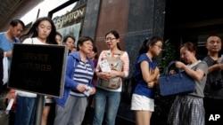 中國遊客在法國一家著名百貨公司門前排隊等候進去購物。