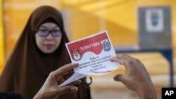 Seorang petugas pemungutan suara memeriksa surat suara saat putaran kedua pilgub Jakarta, 19 April 2017. (Foto: Associated Press)