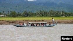 Wara etnis Rohingya mengungsi dengan perahu melewati sungai Buthidaung, Myanmar (foto: ilustrasi). Sedikitnya tiga perahu yang mengangkut pengungsi Rohingya dari Myanmar ke Bangladesh tenggelam, menewaskan 26 orang.