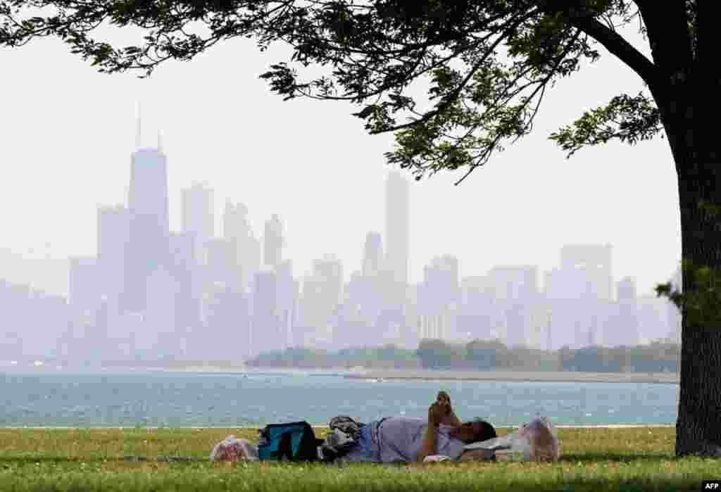 8 tháng 6: Một phụ nữ nằm nghỉ tại một công viên bên bờ hồ ở Chicago vào một buổi trưa nóng bức . (AP Photo/Nam Y. Huh)