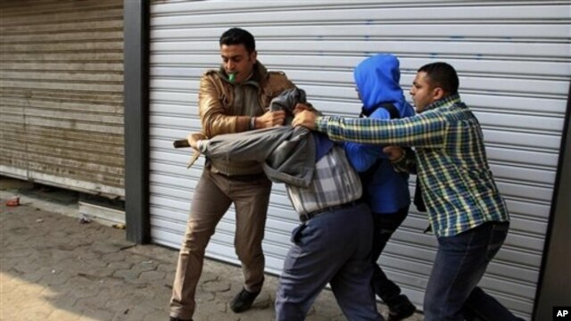 Plainclothes policemen arrest supporter of ousted Egyptian President Mohammed Morsi during clashes in Cairo, Jan. 3, 2014.