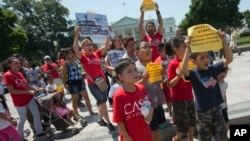 Demonstrators march following a news conference of immigrant families and children's advocates responding to President Barack Obama's position on the crisis of unaccompanied children and families illegally entering the US, in front of the White House in W