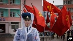 지난 5일 북한 평양의 비 내리는 거리에서 여성 교통보안원이 7차 노동당 대회 깃발을 뒤로 한 채 교통 정리를 하고 있다.