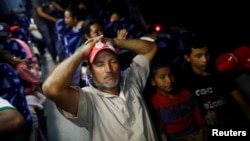 FILE - A Central American migrant, moving in a caravan through Mexico and traveling to request asylum in U.S., gestures inside a bus before his travels from Hermosillo to Mexicali, in Sonora state, Mexico.