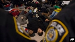 Para demonstran dalam aksi pura-pura mati di Stasiun Grand Central sebagai bagian dari protes melawan keputusan dewan juri New York untuk tidak mendakwa polisi yang membunuh pria berkulit hitam, Eric Garner (6/12). (AP/John Minchillo)