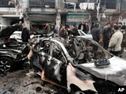 In this photo released by the Syrian official news agency SANA, Syrian citizens and security forces gather next to damaged cars at the scene where an explosion hit a commercial street, in the costal town of Jableh, Syria, Jan. 5, 2017. The blast, which left several killed or injured, undermined a nearly week-old Russia- and Turkey-brokered cease-fire.