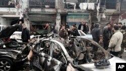 Warga dan petugas keamanan berkumpul dekat mobil-mobil yang hancur akibat ledakan di sebuah jalan daerah komersial, di kota pesisir Jableh, Suriah (5/1). (SANA via AP)