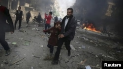 A man holds the hand of a girl as they rush away from a site hit by what activists said were airstrikes by forces loyal to Syria's President Bashar al-Assad, in the Douma, Syria, Nov. 7, 2015.