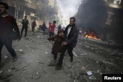 FILE - A man holds the hand of a girl as they rush away from a site hit by what activists said were airstrikes by forces loyal to Syria's President Bashar al-Assad, in the Douma, Syria, Nov. 7, 2015.