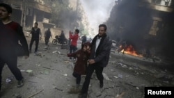 FILE - People rush away from a site hit by what activists said were airstrikes by forces loyal to Syria's President Bashar al-Assad, in Douma, Syria, Nov. 7, 2015. Members of the State Department have expressed their belief that the U.S. should be directly targeting the Assad government with airstrikes.