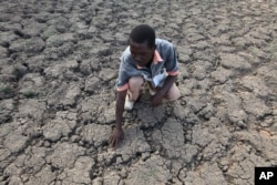 Last Zimaniwa feels the broken ground at a spot which is usually a reliable water source that has dried up due to lack of rains in the village of Chivi , Zimbabwe, Jan. 29, 2016.