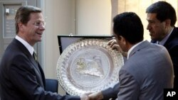 German Foreign Minister Guido Westerwelle (L) shakes hands with Libyan rebel National Transitional Council vice chairman and official spokesman Abdel Hafiz Ghoga after a news conference in Benghazi, Libya, June 13, 2011