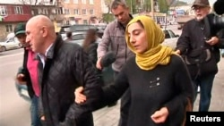 在2013年4月23日的一段视频截屏中显示,记者在马哈奇卡拉追赶波士顿马拉松赛爆炸案两名嫌疑人塔梅尔兰•萨纳耶夫和焦哈尔•萨纳耶夫的母亲朱贝达特•萨纳耶夫