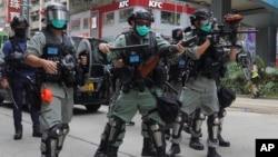Pasukan keamanan Hong Kong menembakkan gas air mata ke arah para demonstran pada aksi protes hari Minggu (24/5).