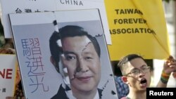 An activist holding a placard showing the merged faces of Taiwan's President Ma Ying-jeou and China's President Xi Jinping, protests against the upcoming Singapore meeting between Ma and Xi, in front of the Presidential Office in Taipei, Taiwan, November