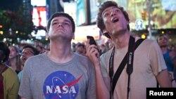 22 yoshli Jasper Goldberg va 22 yoshli Andreas Bastian qo'nish jarayonini tomosha qilmoqda, Tayms maydonida jonli efir, Nyu-York, 6-avgust, 2012-yil.
