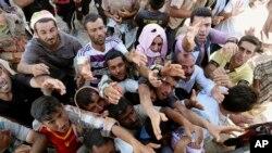 Grupos de civiles se encuentran en refugios acorralados por los yihadistas en una montaña al norte de Irak cerca a la capital kurda.