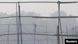 一名劳工在雾霾中的新德里拆除脚手架。(资料照)