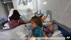 Farida, 7, and her mother lay on the bed at hospital after a militant attack on a Shiite shrine in Kabul, Afghanistan, Wednesday, Oct. 12, 2016. More than a dozen people were killed in the attack on a Shiite shrine in Kabul, an official said. (AP Photo/Rahmat Gul)