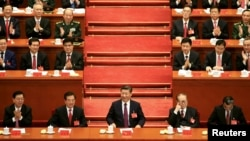 FILE - Chinese President Xi Jinping, center, attends the opening of the 19th National Congress of the Communist Party of China at the Great Hall of the People in Beijing, China, Oct. 18, 2017.