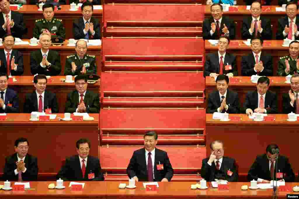 中国共产党第十九次全国代表大会在中国北京人民大会堂开幕。主席台前排从左至右依次是:全国人大常委会委员长张德江,中国前国家主席胡锦涛,中国国家主席习近平,前主席江泽民,国务院总理李克强(2017年10月18日)。照片上,这5个人里只有张德江仍然在鼓掌,而主席台上后面的人除了3人之外都在鼓掌,其中有习近平的亲信、北京市委书记蔡奇,以及国务委员杨洁篪、外交部长王毅等人。
