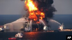 """2010年4月,英国石油公司(BP)在墨西哥的一架名为""""深水地平线""""的钻井平台发生爆炸,救援人员正在努力扑灭大火。"""