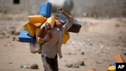 FILE - A boy carries buckets to fill with water from a public tap amid an acute shortage of water Oct. 13, 2015, on the outskirts of Sanaa, Yemen.
