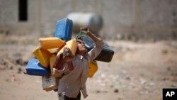 Un garçon porte des seaux à remplir avec de l'eau à partir d'un robinet public au milieu d'une grave pénurie d'eau , à la périphérie de Sanaa , au Yémen , le mardi 13 octobre 2015 .
