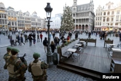 Belgian soldiers stand guard on Brussels' Grand Place, Dec. 30, 2015, after two people were arrested in Belgium on Sunday and Monday, both suspected of plotting an attack in Brussels on New Year's Eve, federal prosecutors said.