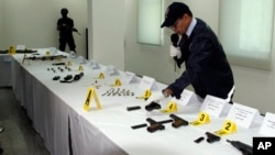 Official with the Central Bureau of Judicial Investigation gestures toward confiscated weapons in Sale, Morocco, Sept. 14, 2015.