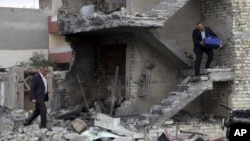 在伊拉克巴格达发生的汽车爆炸之后,人们清理爆炸之后遗留的废墟(2016年1月12日)。