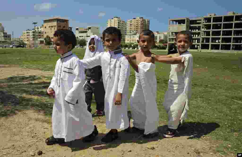 សិស្សសាលាប៉ាឡេស្ទីន ក្នុងសំលៀកបំពាក់ជាជនធម្មយាត្រាមូស្លីម ដើររួមគ្នានៅទីលានធំមួយក្នុងក្រុង Gaza City អំឡុងពេលរៀនមេរៀនអំពីធម្មយាត្រា Hajj ទៅកាន់ក្រុង Mecca ប្រទេសអារ៉ាប៊ី សាអូឌីត។