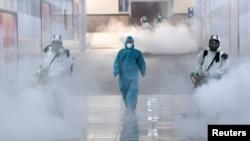 身穿防護服的工作人員在中國湖南長沙市的一個地鐵站里噴撒消毒液防範新冠病毒。(2020年2月4日)