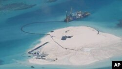 A Chinese vessel, top center, is used to expand structures and land on the Johnson Reef, called Mabini by the Philippines and Chigua by China, at the Spratly Islands in the South China Sea, Philippines.