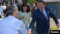 FILE - For the first time in a decade, the party of Bosnian Serb leader Milorad Dodik — who is shown shaking hands with a supporters on the day of elections last October — is not a part of the central government.
