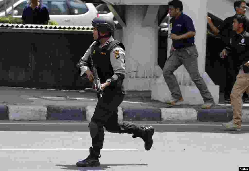 An Indonesian policeman runs near the site of a blast in the center of the Indonesian capital.
