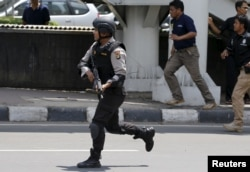 An Indonesian policeman runs near the site of a blast in Jakarta, Jan. 14, 2016.