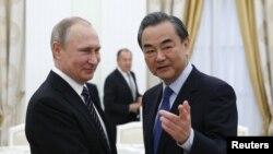 25일 모스크바를 방문한 왕이 중국 외교부장(오른쪽)이 블라디미르 푸틴 러시아 대통령과 만나 악수하고 있다.