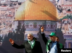 Hamas Chief Ismail Haniyeh and Gaza's Hamas Chief Yehya Al-Sinwar gesture to supporters during a rally marking the 30th anniversary of Hamas' founding, in Gaza City, Dec. 14, 2017. Al Aqsa mosque is in the background.