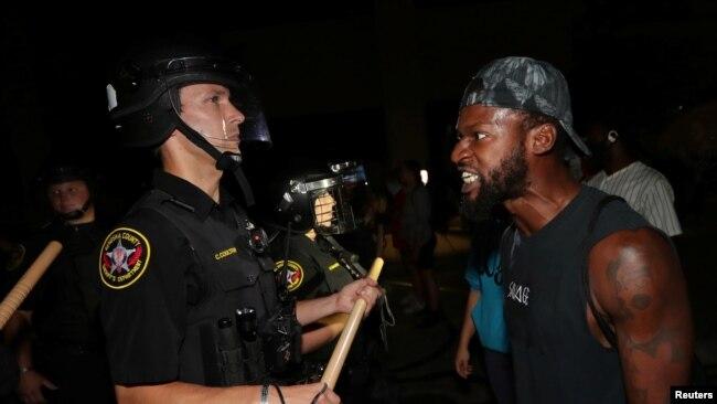 Một người đàn ông đối mặt với nhân viên cảnh sát bên ngoài Sở Cảnh sát Kenosha ở Wisconsin, Mỹ, trong các cuộc biểu tình bùng phát hômg 23/8 sau khi cảnh sát bắn trọng thương Jacob Blake, một người đàn ông da đen.
